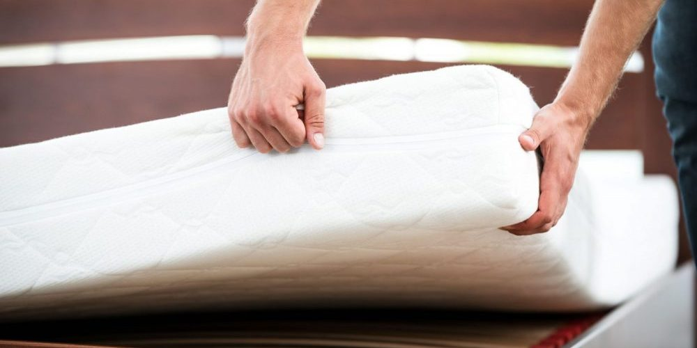 Hands performing mattress removal