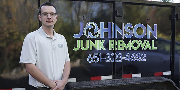 Junk removal expert standing in front of a truck