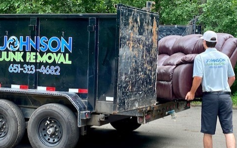 Johnson Junk Removal expert hauling couch on truck
